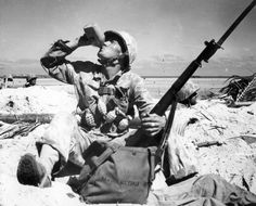 Battle of Tarawa, November 1943: PFC Newcomb takes a swig from his water bottle as the US Marines storm the beach. He carries a healthy supply of hand grenades and ammo for his M1 Garand rifle.