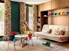 Children's chairs by Arne Jacobsen for Fritz Hansen surround a table in the playroom of decorator Laura Santos's Manhattan townhouse. The sofa is by Ligne Roset, the teak cabinetry is by Poliform, and the curtains and pillows are made of a Clarence House fabric.
