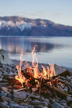 outdoor gevoel; kampvuur ergens in de natuur met een fantastisch uitzicht op het water en de bergen