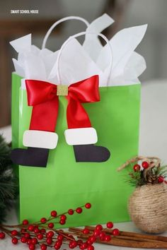 Santa Boot Bows Santa Boot Bows - If you're wrapping gifts for kids this year, you must add some decorative Santa boot bows using red satin ribbon, card stock, and glue. Diy Holiday Gifts, Christmas Gift Bags, Diy Christmas Cards, Homemade Christmas Gifts, Christmas Gift Wrapping, Diy Gifts, Christmas Crafts, Christmas Decorations, Wrapping Gifts