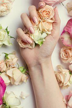Polka dot manicure holding flowers.