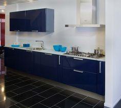 Rotpunkt Lucido  Rechte keuken in een mooi nachtblauwe kleur. Het werkblad is van gehard glas. De keuken heeft ook een kastelement met koelkast en combimagnetron.  Opvallend detail is dat het glazen werkblad doorloopt tegen de achterwand.  Slecht € 4300,00