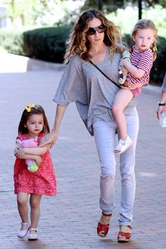 For a day out with her girls, Sarah Jessica Parker donned form-fitted gray jeans. To dress up the outfit, she added a pop of red via Swedish Hasbeens sandals. Photo Credit: Christopher Peterson, BuzzFoto/FilmMagic/Getty Images via StyleList