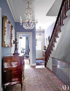 The entry hall of a Manhattan townhouse includes a large Swedish cut-glass chandelier and an Italian parquetry commode, both 18th century.