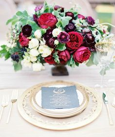 Gold-edged place setting, menu with gold ink calligraphy on black paper, and lush red florals - so rich and elegant!