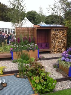 Love the log store / seating idea for a boring garden wall. Tatton Pk Flower show 2011.  NB ground levelled off by plank and filled with gravel (solution for bumpy surface outside our outhouses).
