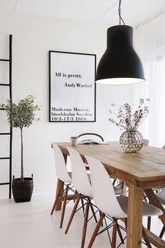 Espace nordique avec table en bois, chaises contemporaines d'esprit vintage, mur blanc et touches de noir (suspension industrielle peinte en noir, pot de fleur noir, échelle noire, rebords du tableau noirs). Inspiration de la nature : fleurs séchées, plante verte, meubles en bois. Touche fantaisie : tableau citation d'Andy Warhol. Décoration scandinave, style nordique : ambiance zen et naturelle, salle-à-manger à l'intérieur de la maison au design épuré ! #plante #fleurs #déco #cuisine…