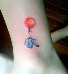 Tiny elephant with red balloon