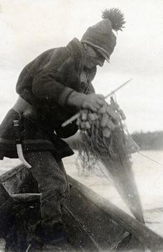 Anders Saitun is fishing with a net. Tjuonajåkk, Girjas Sami community, Gällivare parish, Lapland, Sweden.