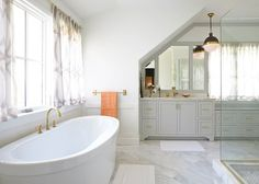 Bright master bath with brass fixtures and marble flooring. #white #bathroom #design