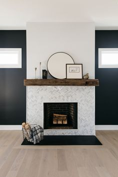 Fireplace features a Reclaimed Wood Beam, Herringbone Marble Tile and Leathered Granite hearth Accent paint color is SW Iron Ore 7069 Modern Marble Tile, Fireplace Remodel, Home, Home Fireplace, Small Fireplace, Farmhouse Fireplace, House Interior, Living Room Inspiration, Home And Living