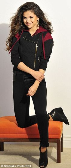 Glossy locks: Selena showed off her thick tousled curled brown hair, paired with subtle make-up and hooped earrings