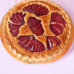 Tarta de peras y almendras  Base de tarta, crema de almendras y peras al vino tinto fileteadas en la superficie.