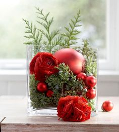 fill a vase with juniper sprigs, evergreen branches, ornaments and cut flowers