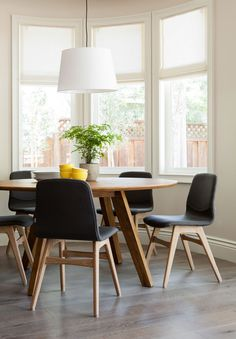 Designer Jennifer Jones of Niche Interiors creates an eco-friendly home that emphasizes clean lines and encourages sustainable living. In a dining room of her design, a triptych of windows overlooks a round table from Crate & Barrel.