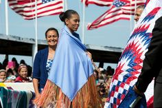 First Lady Michelle Obama wears a shawl presented to her by Tribe Chairman Dave Archambault II and Mrs. Nicole Archambault during the Cannon Ball Flag Day Celebration at the Cannon Ball powwow grounds, during a visit to the Standing Rock Sioux Tribe Reservation in Cannon Ball, N.D., June 13, 2014. (Official White House Photo by Pete Souza)