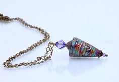 The paper bead is made from Japanese hand silk-screened paper in colours of mauve, turquoise and red on a core of recycled water-colour paper.  An 8mm mauve swarovski crystal bicone bead sits above the paper bead and cast bronze cap. A 3mm swarovski crystal sits at the bottom tip of the pendant. The paper bead is hand rolled and finished with numerous layers of varnish to make a strong and durable bead. It is finished with a wax coating to impart a soft sheen.