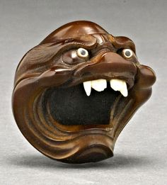 Demonic Head Netsuke in Boxwood. Meiji periodCarved as a demonic head with a wide open mouth inlaid with bone fangs and bushy eyebrows framing large eyes of horn and mother-of-pearl, signed Chokuichi/Naokazu.