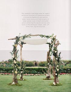 Pérgola altar aire libre con troncos y flores blancas para boda