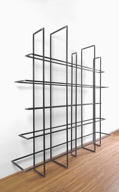 Grid, made up of 10 metal frames that as a free standing bookcase or as a room divider can be used. The 'boards' have different widths and are open in the middle. This makes them suitable for some books, but also something can be hung in. A metal container (accessory), can serve as a planter or to put other stuff in.  The open frames deliver an exciting game of lines. Depending on where you're standing some of the shelves appear to float.  Design: Gerard de Hoop