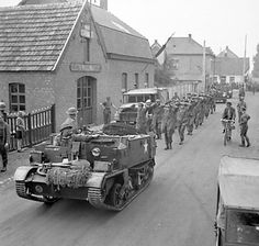 Men of 158 Brigade, UK 53rd (Welsh) Division escorting German prisoners, the Netherlands, 19 Sep 1944; note Universal Carrier leading the co...