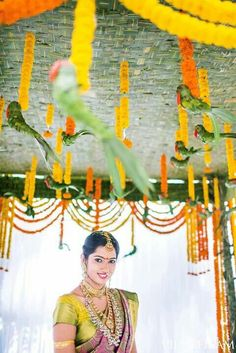 Bride posing at the wedding 'mandap' decorated with mariglds
