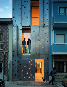 The symbol-perforated aluminum facade of José Cadilhe's narrow House 77 in Portugal. The metal shutters cover full-height windows.