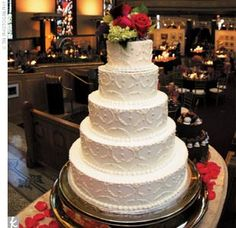 The cake featured flavors of white chocolate with mocha and raspberry, lemon with raspberry and mocha, and orange butter cake with fresh strawberries and cream-cheese buttercream. The cake was designed to mimick the detail on Bobby's wedding gown and was topped with a tiara cake topper filled with flowers.