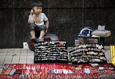 A child talks on his mobile phone as he looks after a street jewelry vender, June 11, 2012 in Shanghai, China. (Eugene Hoshiko/Associated Press)