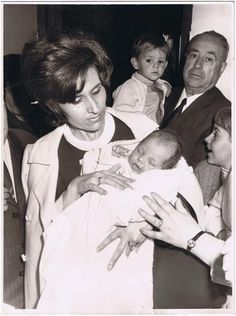 La foto es del bautizo César Cabrera en Docamar. En la foto le sostiene en brazos su madre Virtudes y al fondo su abuelo Donato (quien da nombre al Docamar) sosteniendo a su hermano Raúl. Los dos niños son la actual tercera generación que dirige Docamar.