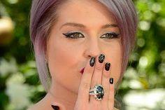 """Kelly Osbourn ama laccare le sue unghia di nero, chi altri se non lei poteva acquistare """"Black Diamond Nail Polish"""", lo smalto più costoso al mondo che ha al suo interno ben 267 carati di diamanti neri. Per i capelli ha scelto una tintura grigio-viola, per il make up eye liner nero e viola e rossetto rosso."""