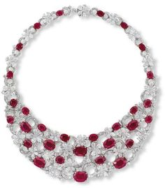 Lot 1988 - An Important Ruby & Diamond 'Flora' Necklace, by Bulgari The bib necklace, designed as an openwork panel of thirty oval-shaped rubies weighing approximately from 7.00 to 1.21 carats, connected by keystone and whistle-cut diamond overlapping circular links, interspersed by pear-shaped diamond florets, accented by brilliant-cut diamonds, extending to the backchain, mounted in 18k white and yellow gold, 36.0 cm long, in black leather Bulgari case
