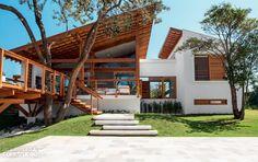 Casa incorpora árvore no deck e se beneficia de sua sombra. Projeto de Bela…