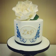 blue hand-painted cakes   Hand painted cake in royal blue, gold monogram & white sugar rose
