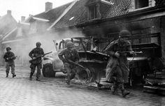 American paratroopers of the 101st Airborne Division walk past a destroyed truck in the town of Veghel, 1944. #WW2