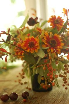 A fall centerpiece with berries, zinnias, cosmos, and cherries.