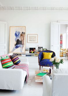 I am loving the look of this living space.  White backdrop with pops of color in the chair, pillows and artwork.  Plus there's that yellow quilt draped on the armchair in the background.  What's not to love?