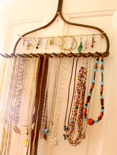 An eclectic item, repurposed metal rake head used as a jewelry rack.