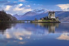 Eilean Donan Castle surrounded by mountains Eilean Donan, Beautiful Beaches, About Uk, Britain, Spanish, Scenery, Highlands Scotland, Tours, Island