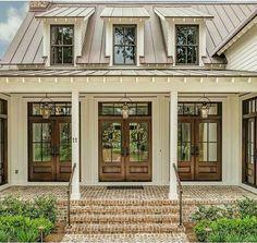 Brick steps. Brown metal roof. Doors.