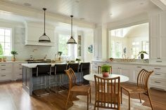 Two white glass and bronze pendants hang from a white shiplap ceiling above a charcoal gray kitchen island accented with a white marble countertop fitted with a sink paired with a polished brass deck mount faucet.