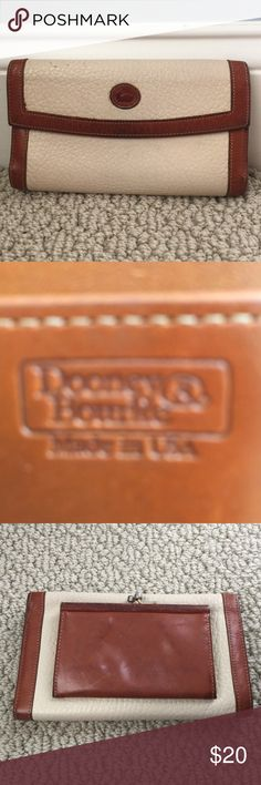 Authentic vintage Dooney & Bourke ladies wallet. Genuine leather with brass metal on change purse side.  Brown leather trim coloring alterations with use.  Cream leather with ink spot X1 (upper left of pic).  Check book area and card slots noted inside.  Change purse with patina marks inside- probably from the copper pennies. Dooney & Bourke Bags Wallets