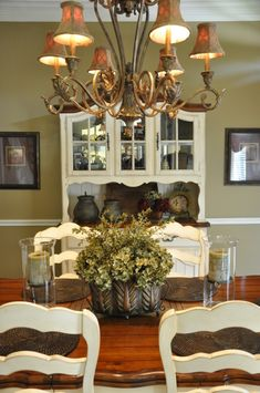 Classy country chic dining room. Love the china cabinet, table, chairs, green accents & chandelier.