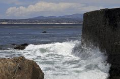 Waves crash against the stone wall surrounding the Monterey Bay, California