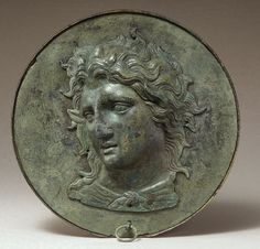 After his death in 323 BCE, Alexander the Great became a popular model for many Greek deities - in this case Pan. Pan is identified by his goat like ears, horns; and since his legs are not shown, small goat hooves tied around his neck. A bronze Box Mirror with the head of Pan, 4th C. B.C.E. Greek. Lifting the ring below the hammered relief reveals a a highly polished bronze disk used as a mirror.