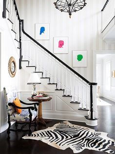 Accentuate the loftiness of the entryway staircase area with a dashing wallpaper that spans several floors. This understated stripe draws the eye up and brightens the airy space.