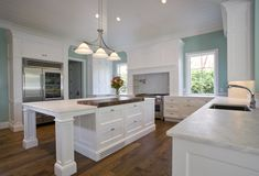 Light mint blue paint adds burst of color to this all-white kitchen over natural hardwood flooring. Large central island features raised wood countertop over marble space, with full dining area on left.
