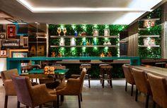 Lounge Bar - As arquitetas Lara Cerantola e Isabella Lolli Ghetti equilibram as texturas de espelhos, madeira, metal e tecidos no ambiente de 120 m², onde funciona uma temakeria. Além das mesas, as bancadas surgem como uma opção informal para as refeições, que ficam mais agradáveis graças à refrescante parede viva. A iluminação bem trabalhada destaca os objetos e as gravuras do artista Juarez Machado.