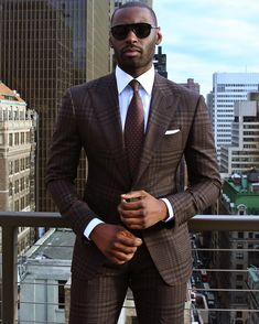 men's dark brown plaid suit, light blue oxford shirt, brown tie, white pocket square