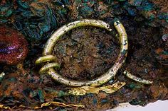 A Celtic coin hoard discovered on the isle of Jersey has presented archaeologists with a wealth of gold treasures. Jersey Heritage's conservation team have been excavating an area known to contain gold jewellery. Late in Dec 2014, one end of a solid gold torc was uncovered.The find follows the discovery of two other solid gold torcs. The latest artefact is considerably larger than anything previously unearthed on the island.